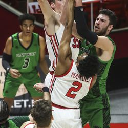 UVU Wolverines forward Evan Cole (2) scores over Utah Utes center Branden Carlson (35) and Utah Utes guard Ian Martinez (2) during a game at the Huntsman Center in Salt Lake City on Tuesday, Dec. 15, 2020.