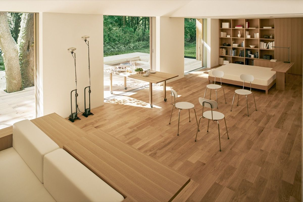 Living room with pale wood floors and wood and white fabric furniture.