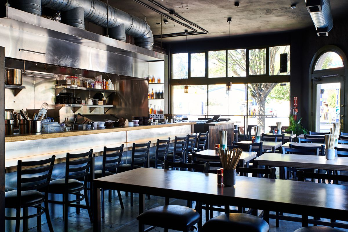 A picture of the dining room at Hapa, with a counter along the chef's pass and long communal tables