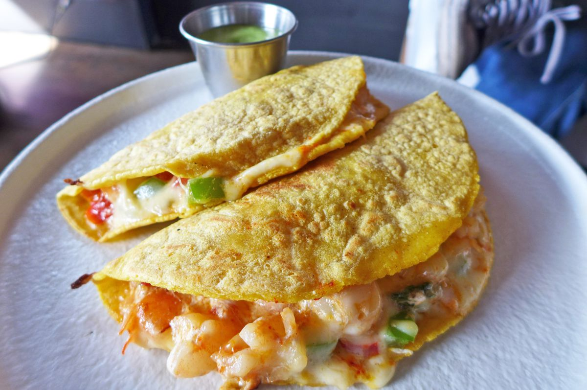 A pair of yellow corn tortillas folded over a shrimp filling.