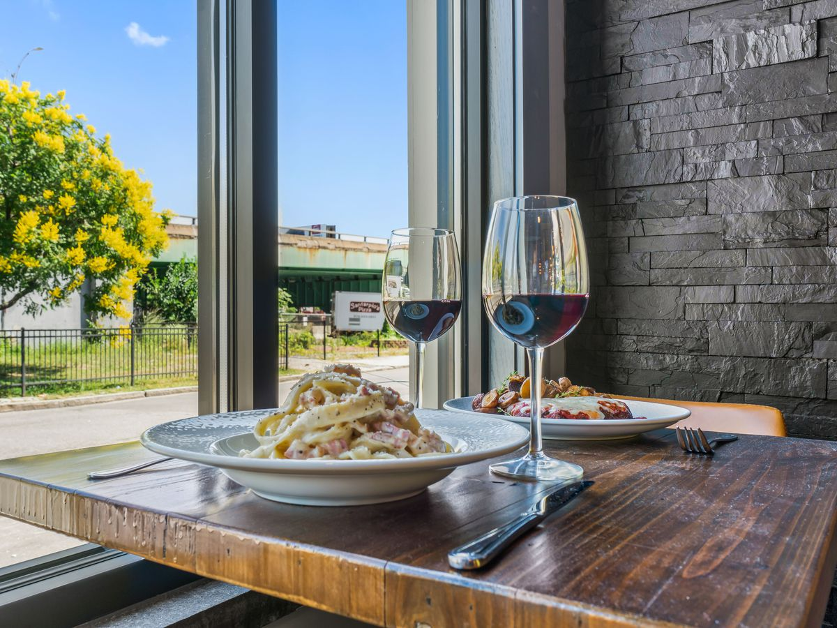 Two plates of carbonara and two glasses of red wine sit atop a high-top table