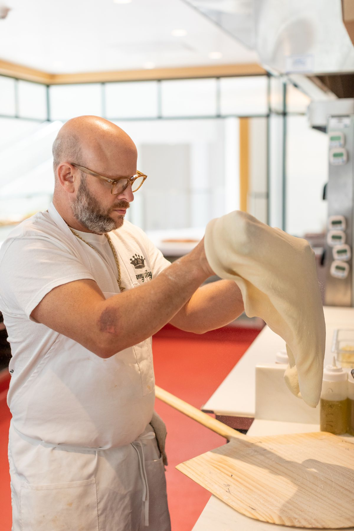 A chef stretches dough for pizza onto a wood peel.