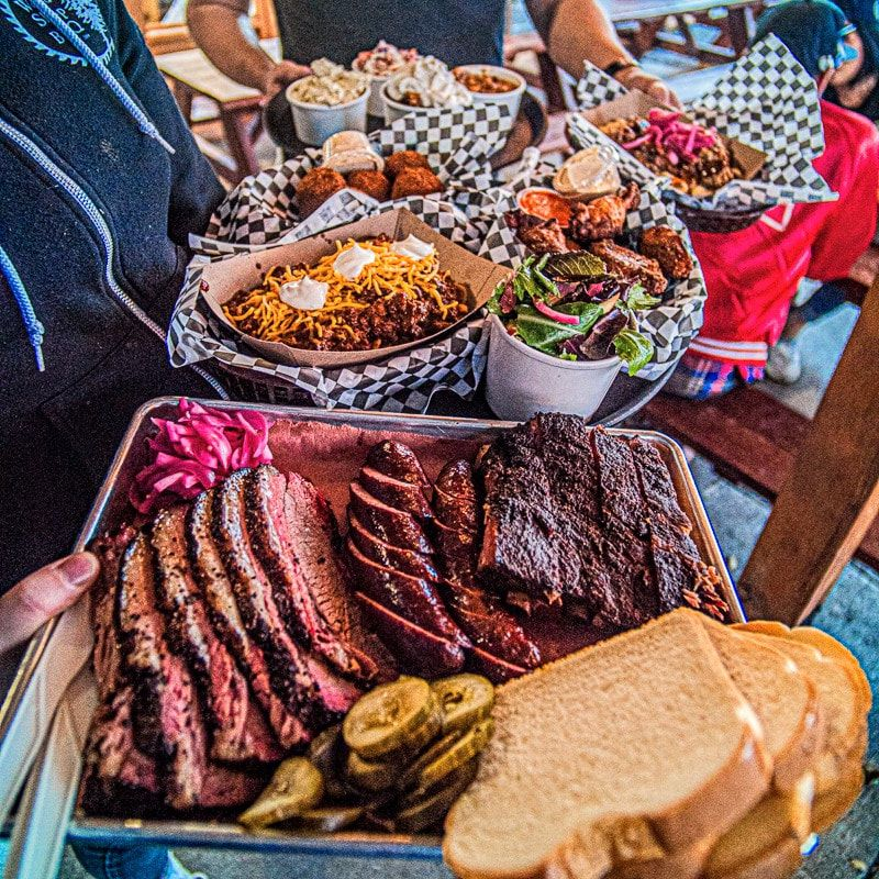 A tray of brisket from Wood Shop BBQ with an array of other barbecue dishes.