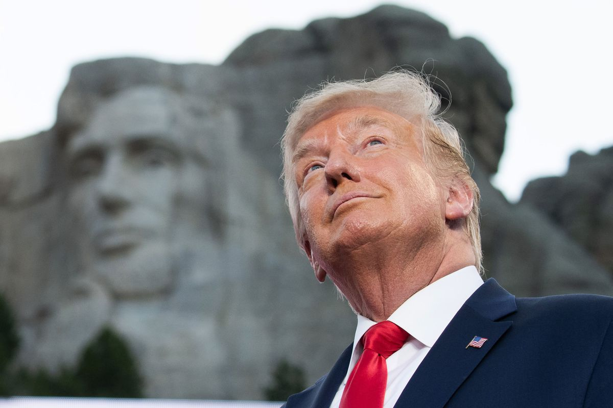 President Trump stands, smiling, with Mount Rushmore behind him.