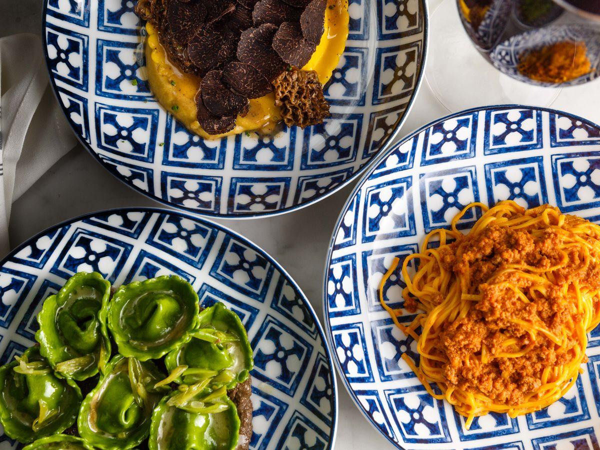 Uovo pasta, cappelletti, tagliolini al ragu sit on elegant blue and white plates at Rezdora