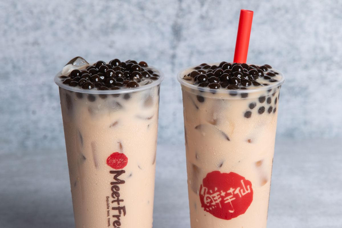 Two cups of milk tea filled to the brim with tapioca boba balls.