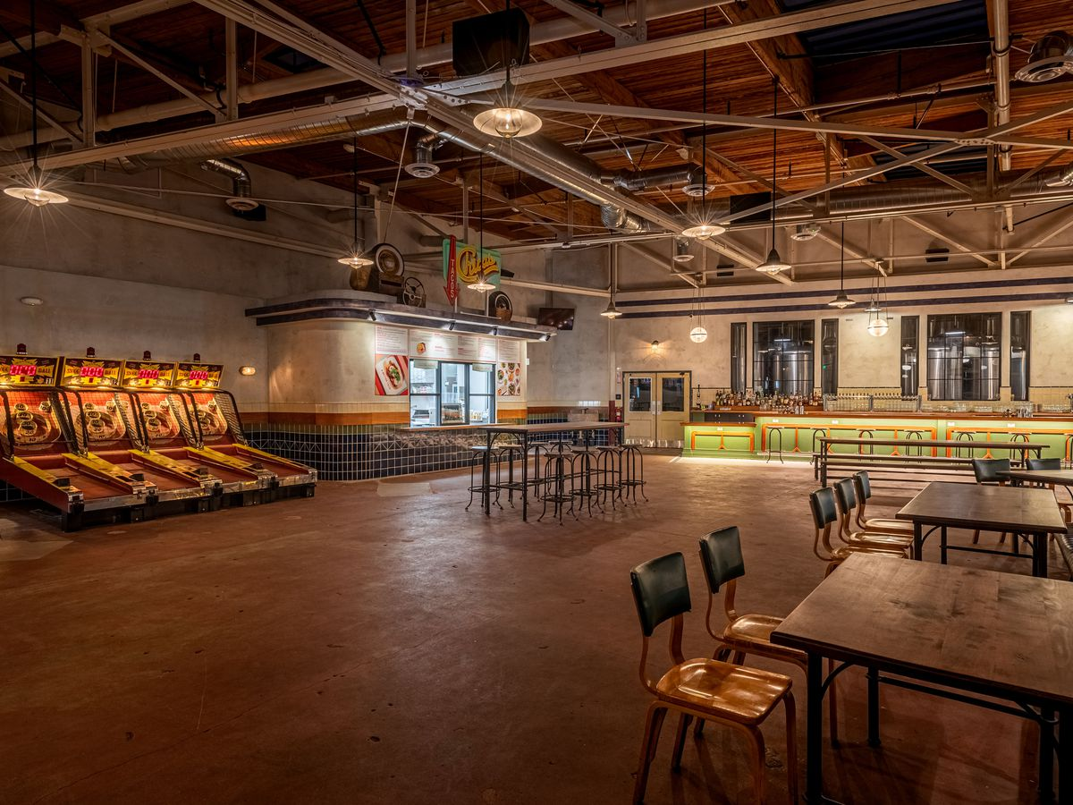 A long open warehouse room with a taco stand in the corner.