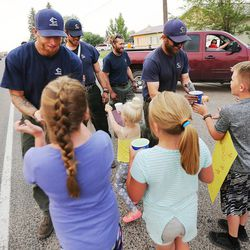 The Lewis & Clark Hotshots out of Montana are greeted by kids with doughnuts and lemonade as fire crews return from fighting the Brian Head Fire near the town of Panguitch on Tuesday, June 27, 2017.