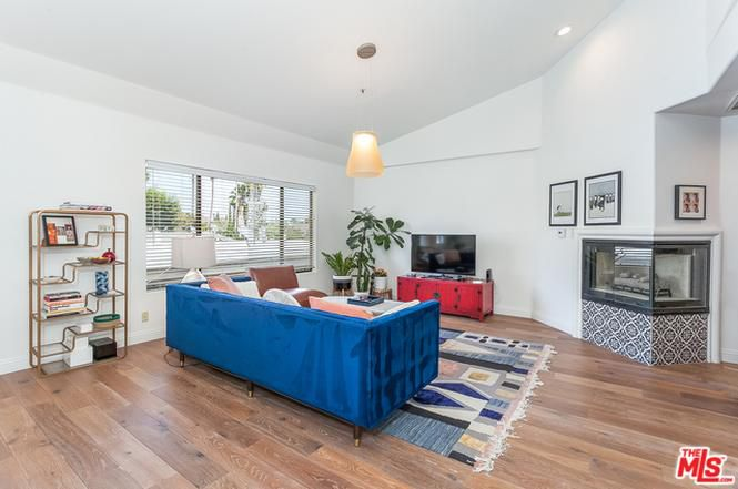 A living room with tall ceilings, recessed lighting, a royal blue velvet sofa, and a gas fireplace.