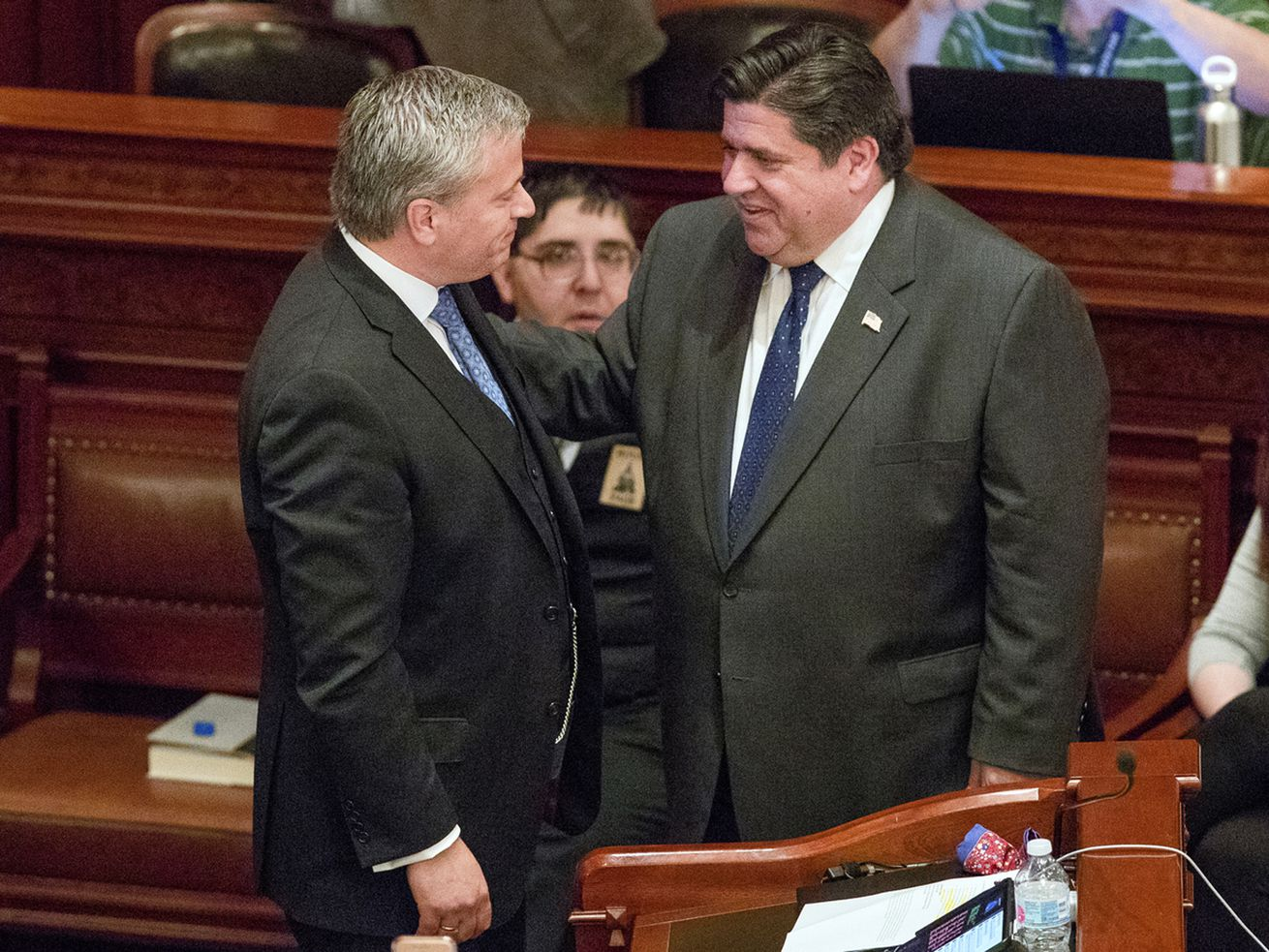 State Rep. Robert Martwick, D-Chicago, left, greets Gov. J.B. Pritzker on the Illinois House floor after the bill to put Pritzker's graduated income tax proposal on the November 2020 ballot passed on Memorial Day.