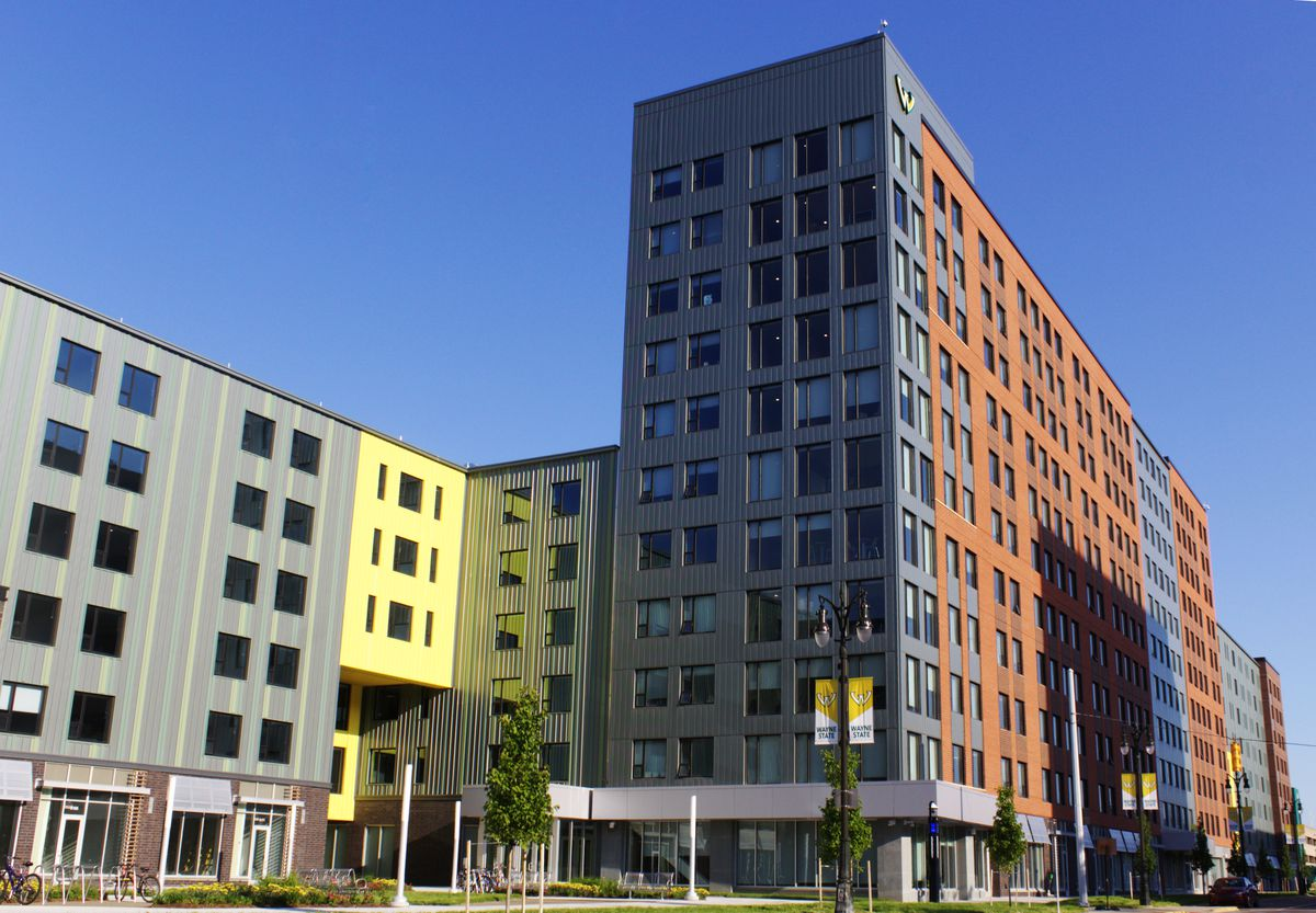 A row of tall, rectangular buildings with repeating windows on every floor. Each panel has its own color: gray, yellow, blue, and brown. There's ground floor retail and modest landscaping.