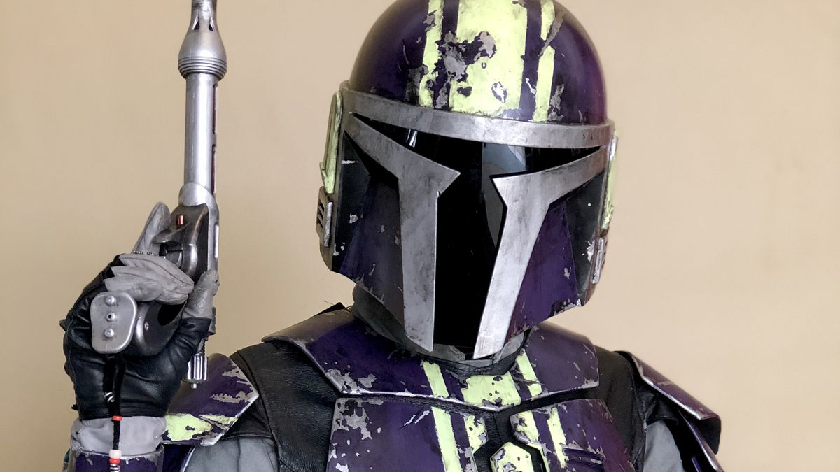 a woman stands holding her gun in purple mandalorian armor
