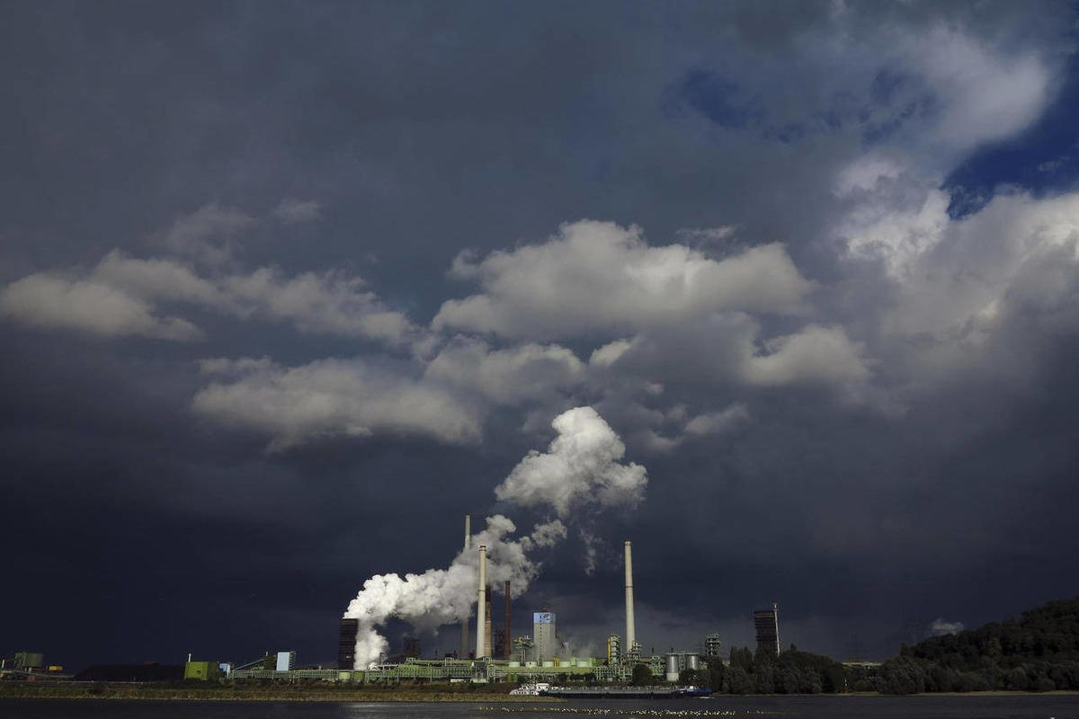 FILE - This Sept. 19, 2012 file photo shows dark clouds filling the sky after a rain shower, behind the ThyssenKrupp Kokerei Schwelgern steel plant on the river Rhine in Duisburg, Germany.  Business optimism in Germany fell for the fifth month in a row, a
