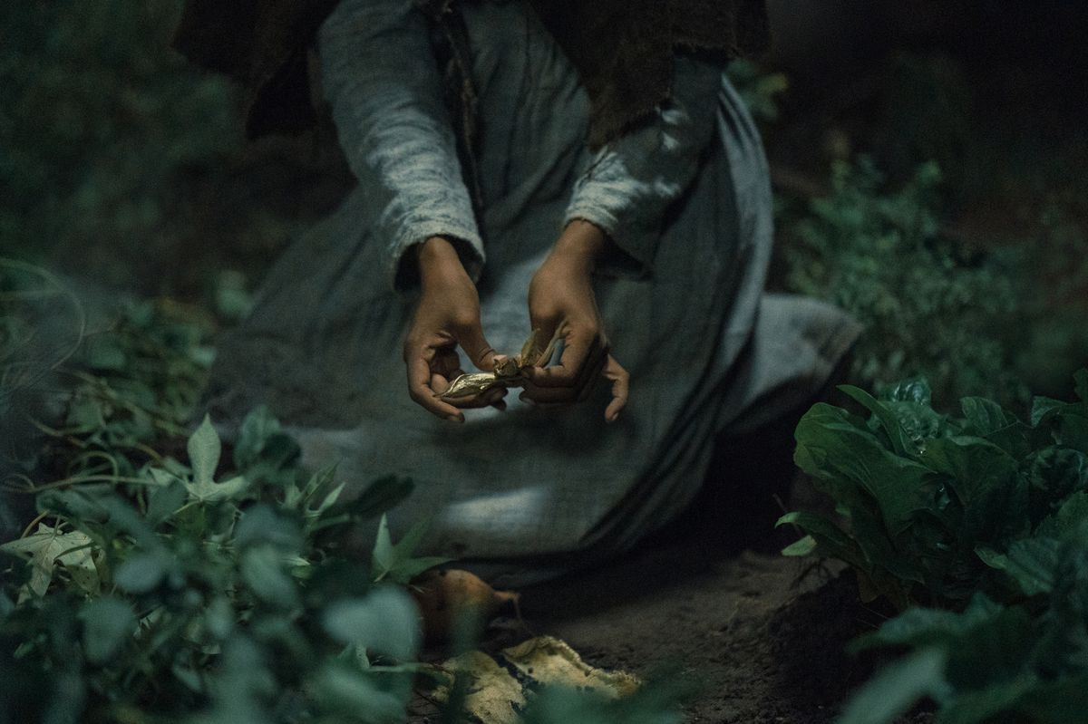 A Black woman in a rough homespun dress holds a small gold object in Barry Jenkins' Underground Railroad