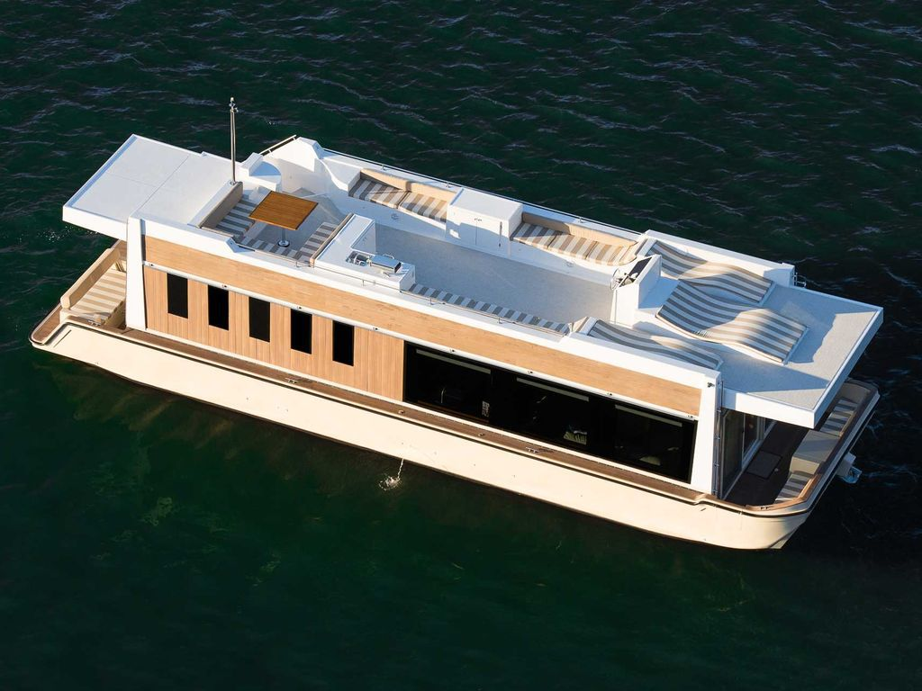 A wide, relatively flat, tan houseboat with an expansive rooftop deck.