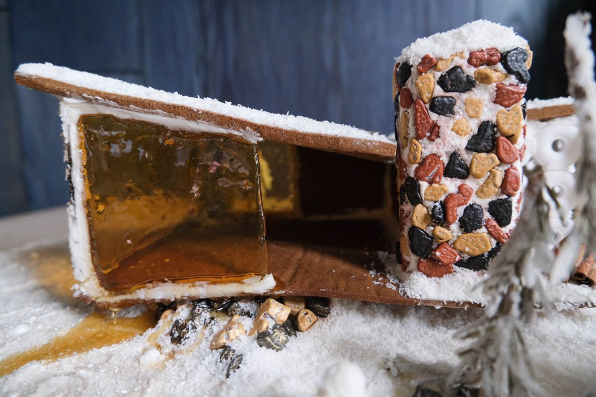 Detail shot of midcentury modern gingerbread house with candy rocks for chimney.
