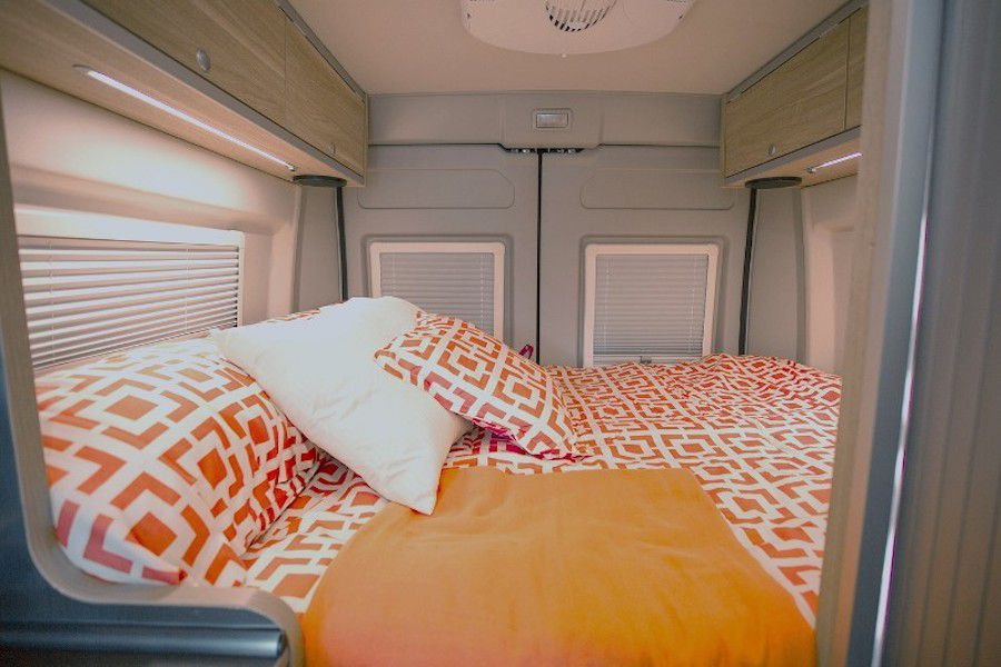 The interior of a RV camper van. The room has a bed that fills the space. The bed has orange and white patterned bed linens.