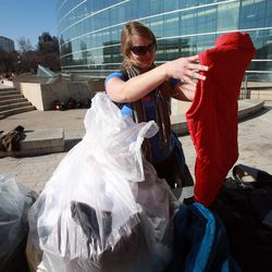 Laura England picks out clothes to deliver to people at Pioneer Park while volunteering at the Community Coat Exchange in the Salt Lake City Library Plaza in Salt Lake City on Friday, Nov. 29, 2013.