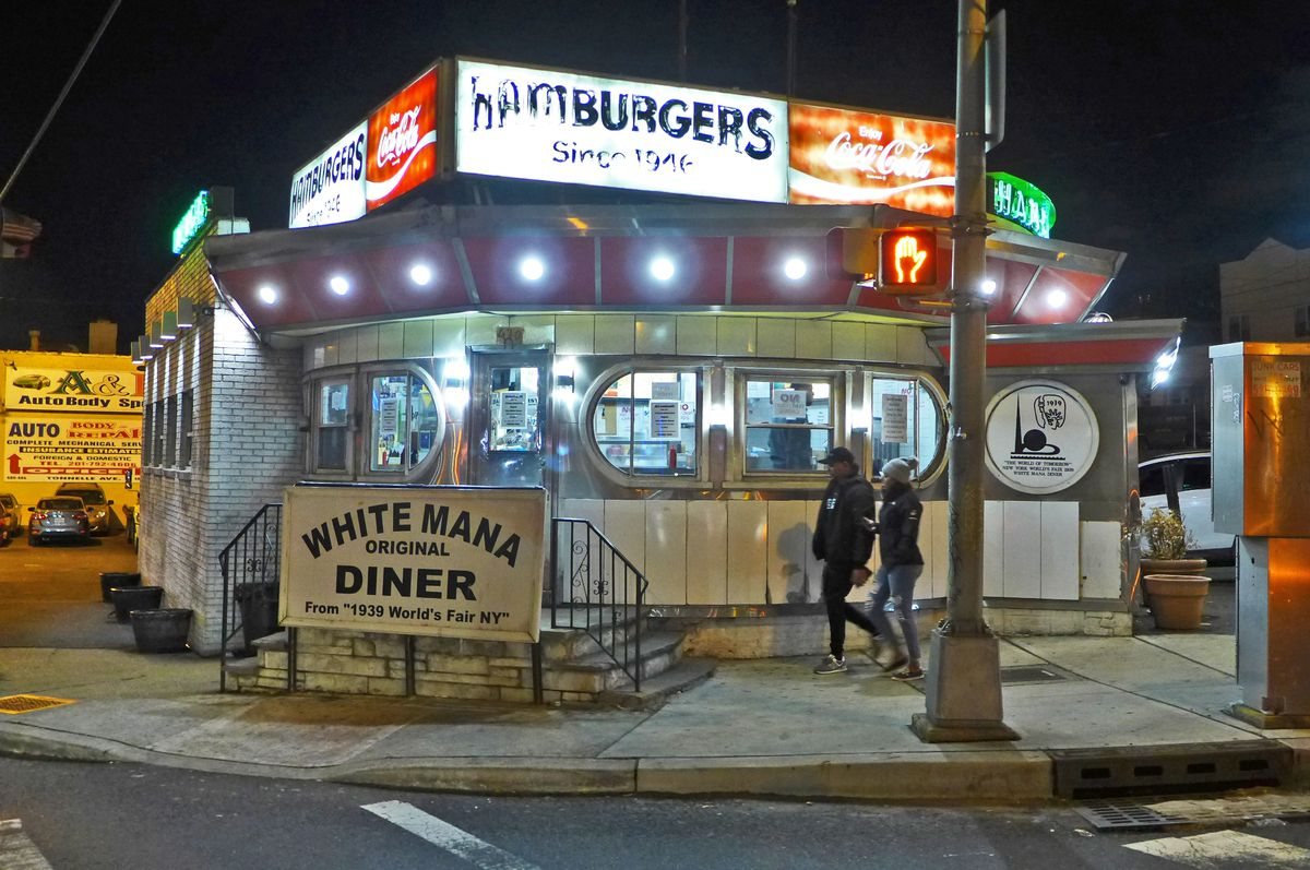 A circular diner by the roadside seen at night.