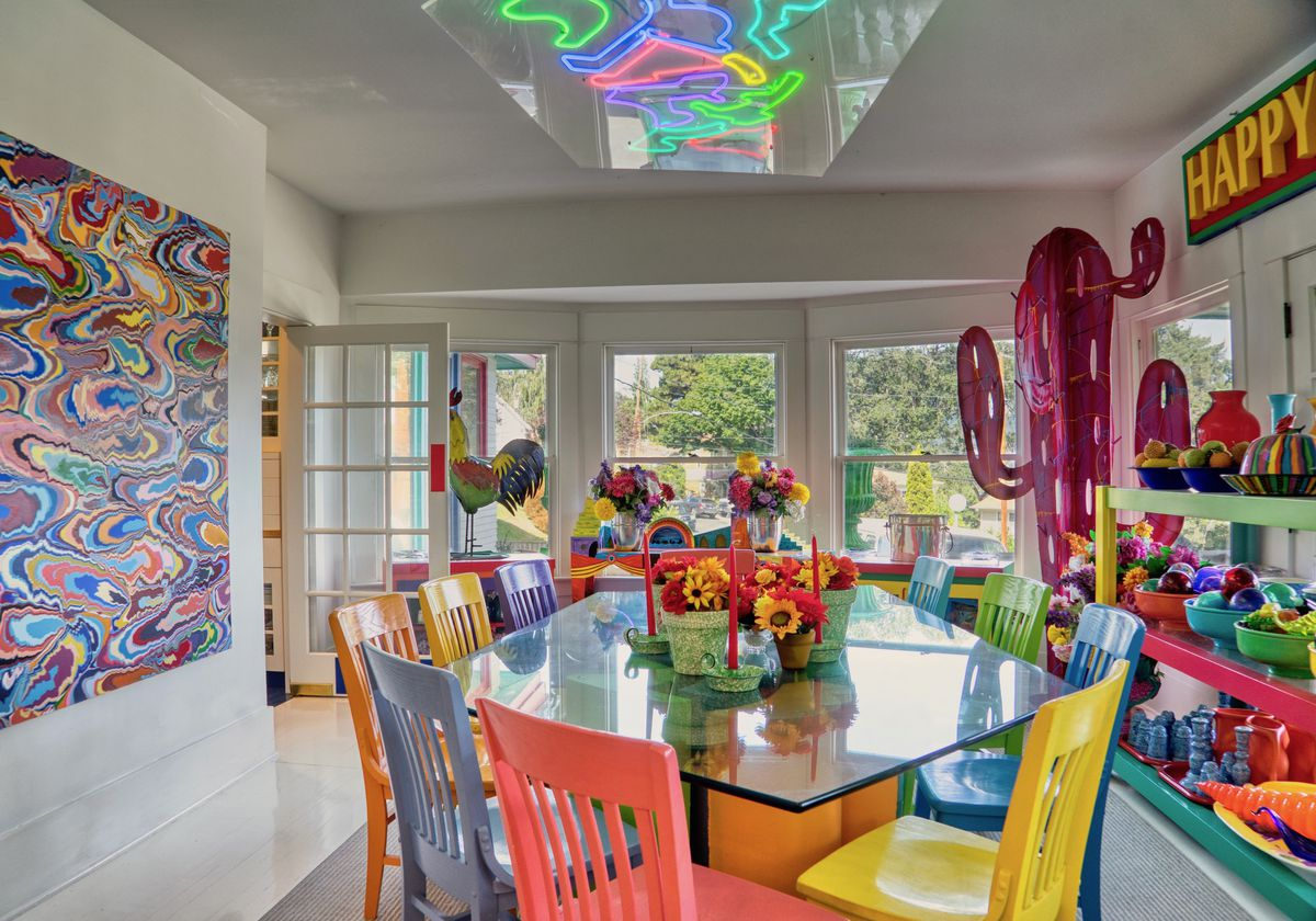 A dining room features a glass table with multi-color chairs and a neon chandelier above.