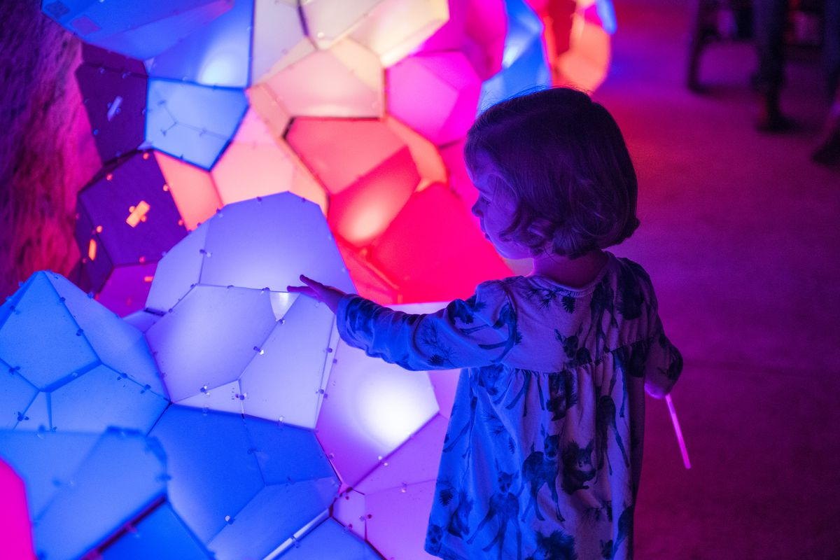 A young girl touching glowing colorful sculpture