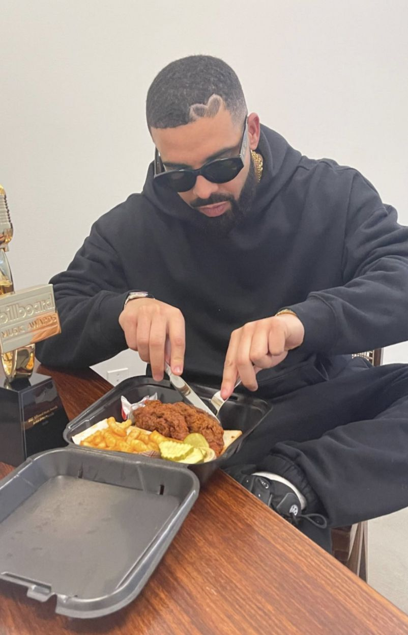 Rapper Drake in a black sweatsuit cuts into a container of chicken tenders and fries from Dave's Hot Chicken.
