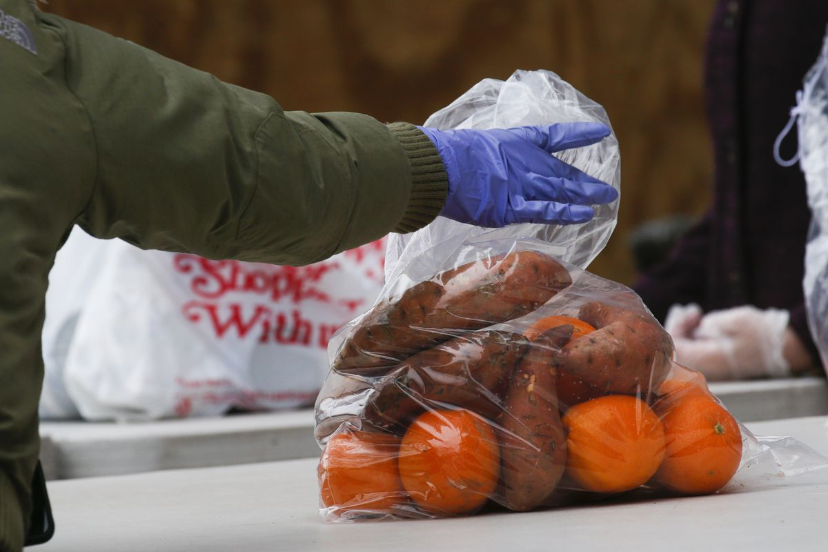 A gloved hand holding a clear plastic bag filled with fruit and vegetables