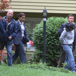 Annie Dookhan, right, is escorted to a cruiser outside her home in Franklin, Mass. Friday, Sept. 28, 2012. Dookhan is accused of faking drug results, forging signatures and mixing samples a state police lab.  State police say Dookhan tested more than 60,000 drug samples involving 34,000 defendants during her nine years at the lab. Defense lawyers and prosecutors are scrambling to figure out how to deal with the fallout.