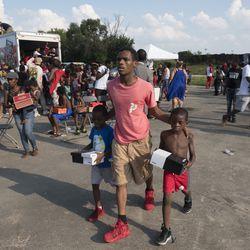 "Crowds mass behind ""anti-bait"" trucks for free shoes.   Rick Majewski/For the Sun-Times"