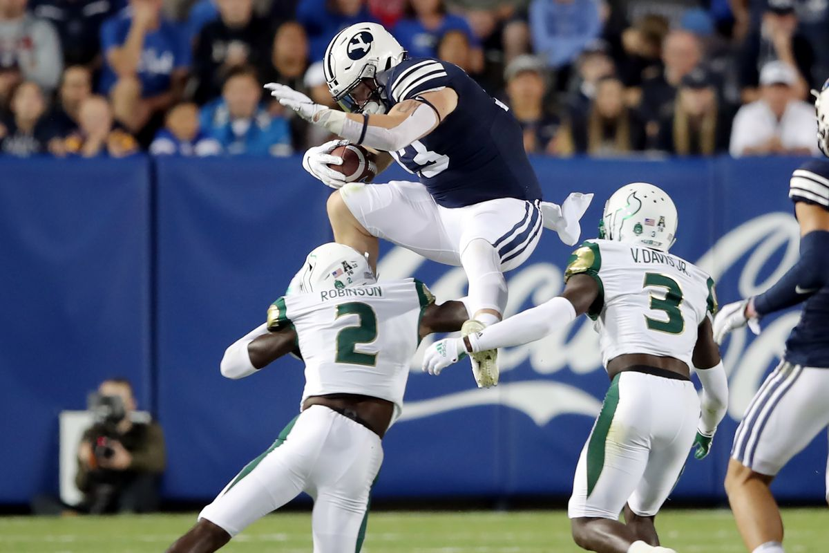 Brigham Young Cougars fullback Masen Wake (13) tries to hurdle South Florida Bulls defensive back TJ Robinson (2) on a run as BYU and USF play a college football game at LaVell Edwards Stadium in Provo on Saturday, Sept. 25, 2021.