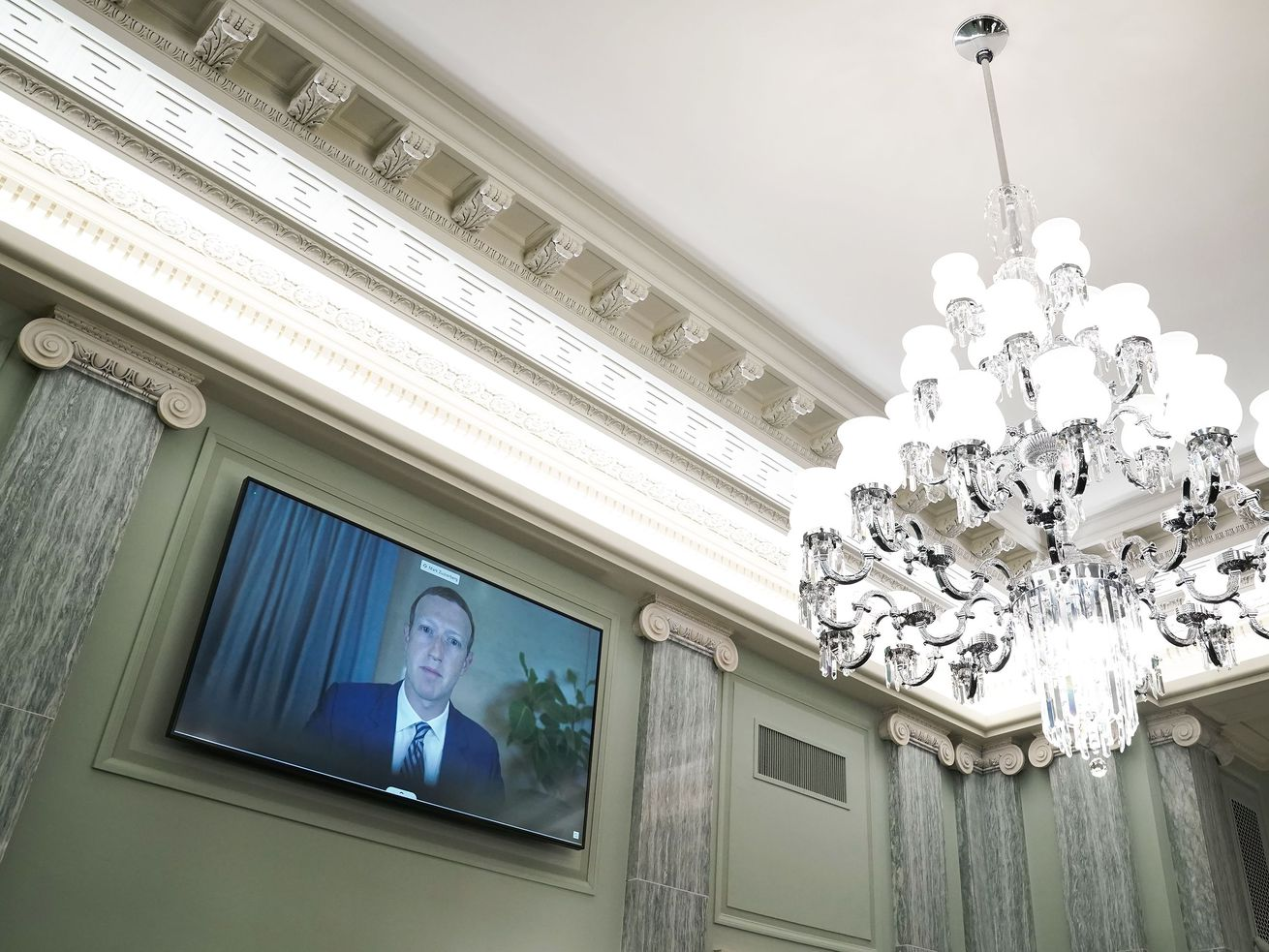Facebook CEO Mark Zuckerberg appears on a screen on the wall of the Senate beside a large chandelier.