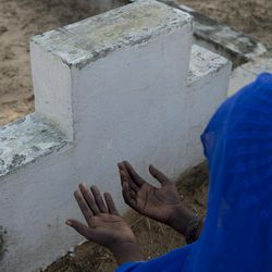 A grieving relative kneels in prayer in front of an unmarked grave, as Catholic and Muslim clerics offered prayers for victims of the 2002 Joola ferry disaster at a cemetery containing 140 unmarked graves in Mbao, outside Dakar, Senegal, Wednesday, Sept. 26, 2012, the tenth anniversary of the ferry's sinking. With an official death toll of 1,863 and only 64 survivors, the Joola disaster remains one of the deadliest in maritime history, surpassing by a large margin the death toll of roughly 1500 in the 1912 sinking of the Titanic.