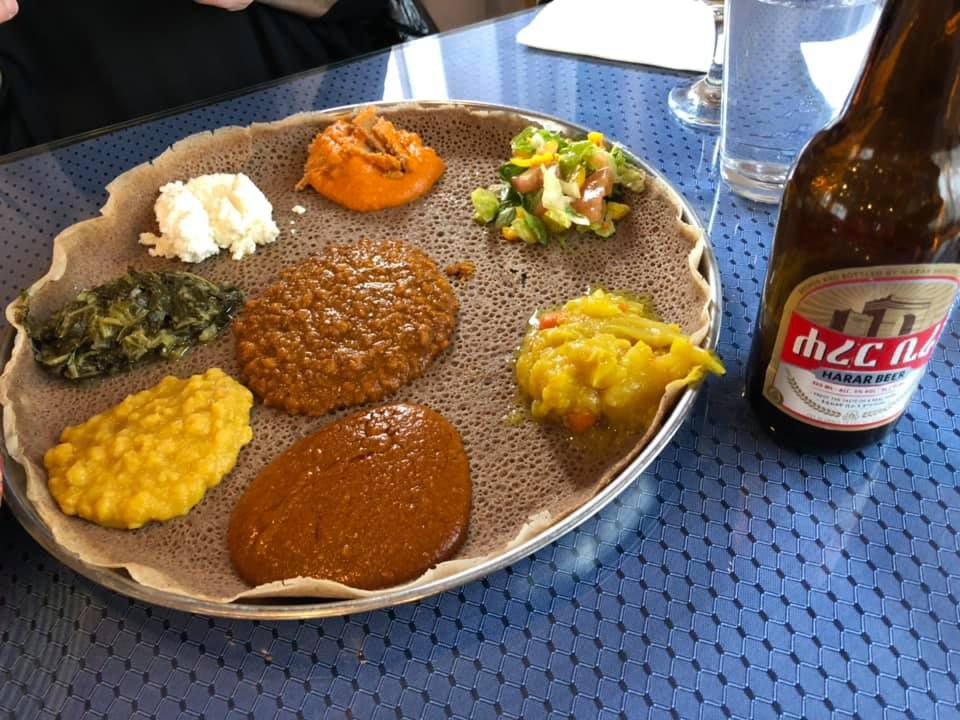 Meskel's injera topped with vegetables and meat, next to a bottle of beer.