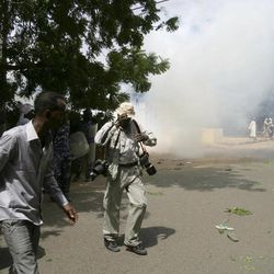 Sudanese protesters and a photographer react to tear gas during a demonstration in Khartoum, Sudan, Friday, Sept. 14, 2012, as part of widespread anger across the Muslim world about a film ridiculing Islam's Prophet Muhammad. Germany's Foreign Minister says the country's embassy in the Sudanese capital of Khartoum has been stormed by protesters and set partially on fire. Minister Guido Westerwelle told reporters that the demonstrators are apparently protesting against an anti-Islam film produced in the United States that denigrates the Prophet Muhammad.