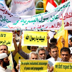 """Iraqis chant slogans during a protest in Basra, 340 miles (547 kilometers) southeast of Baghdad, Iraq, Friday, Sept. 14, 2012. In Basra, about 1,000 Iraqis marched the streets and burned the American and Israeli flags. """"Freedom doesn't mean offending two billion Muslims,"""" one banner said."""