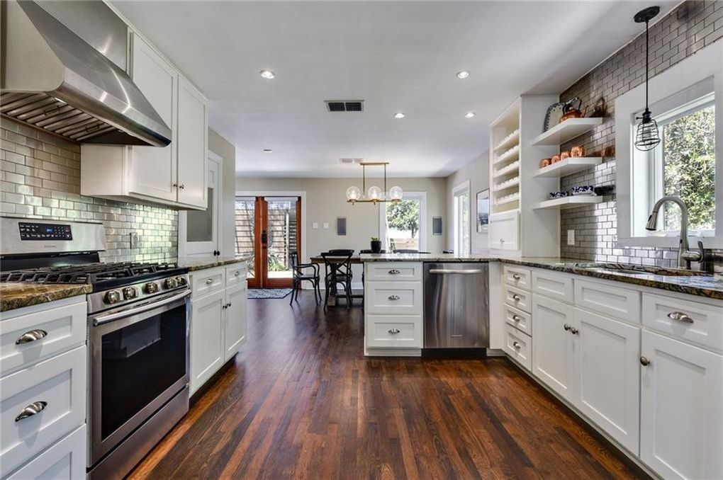 A kitchen with a peninsula features white cabinets, subway tile backsplash, and stainless steel appliances.
