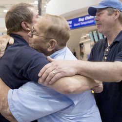 Michael Reed, left, meets his father Dennis Fay and brother Michael Fay for the first time at the Salt Lake City International Airport on Friday, May 15, 2015. Reed, who was placed for adoption after his birth, just found information on his birth father five months ago and flew to Salt Lake City from Chicago to meet him.