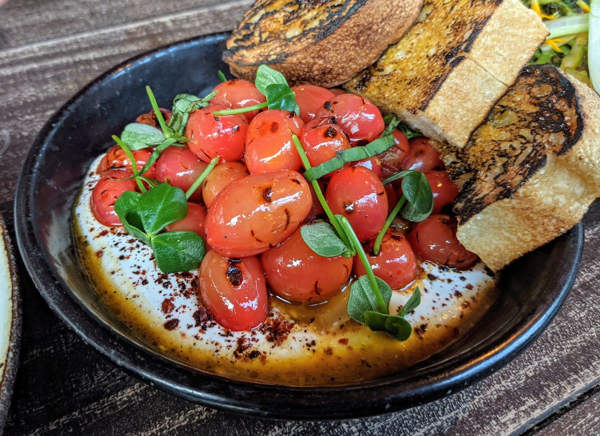 A bowl of dressed cherry tomatoes with toasted bread.