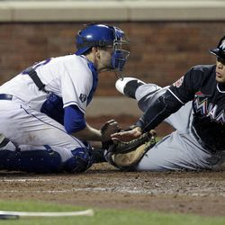 Miami Marlins' Giancarlo Stanton, right, slides safely into home plate past New York Mets catcher Josh Thole on a double hit by Gaby Sanchez during the seventh inning of the baseball game Tuesday, April 24, 2012, at Citi Field in New York.