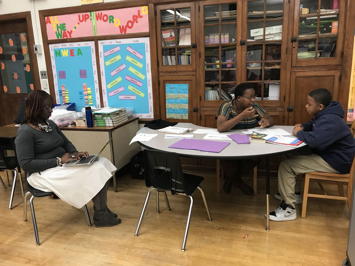 Bethune Elementary-Middle School Principal Alisanda Woods listens in as sixth-grade teacher Samantha Vann meets individually with students.