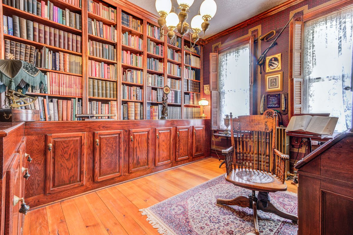A study with built-in bookshelves along one wall and a desk along the other. Windows have shutters and lace curtains.