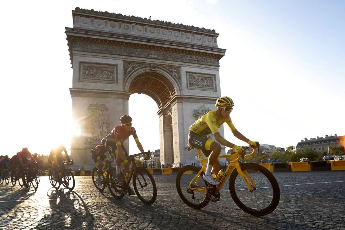 Colombia's Egan Bernal wearing the overall leader's yellow jersey, center, rides past the Arc de Triomphe on the Champs-Elysees