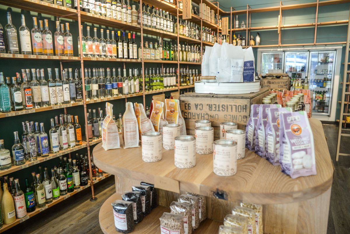 Shelves of liquor and a table of food products.