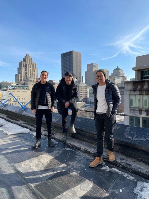 three men standing on rooftop