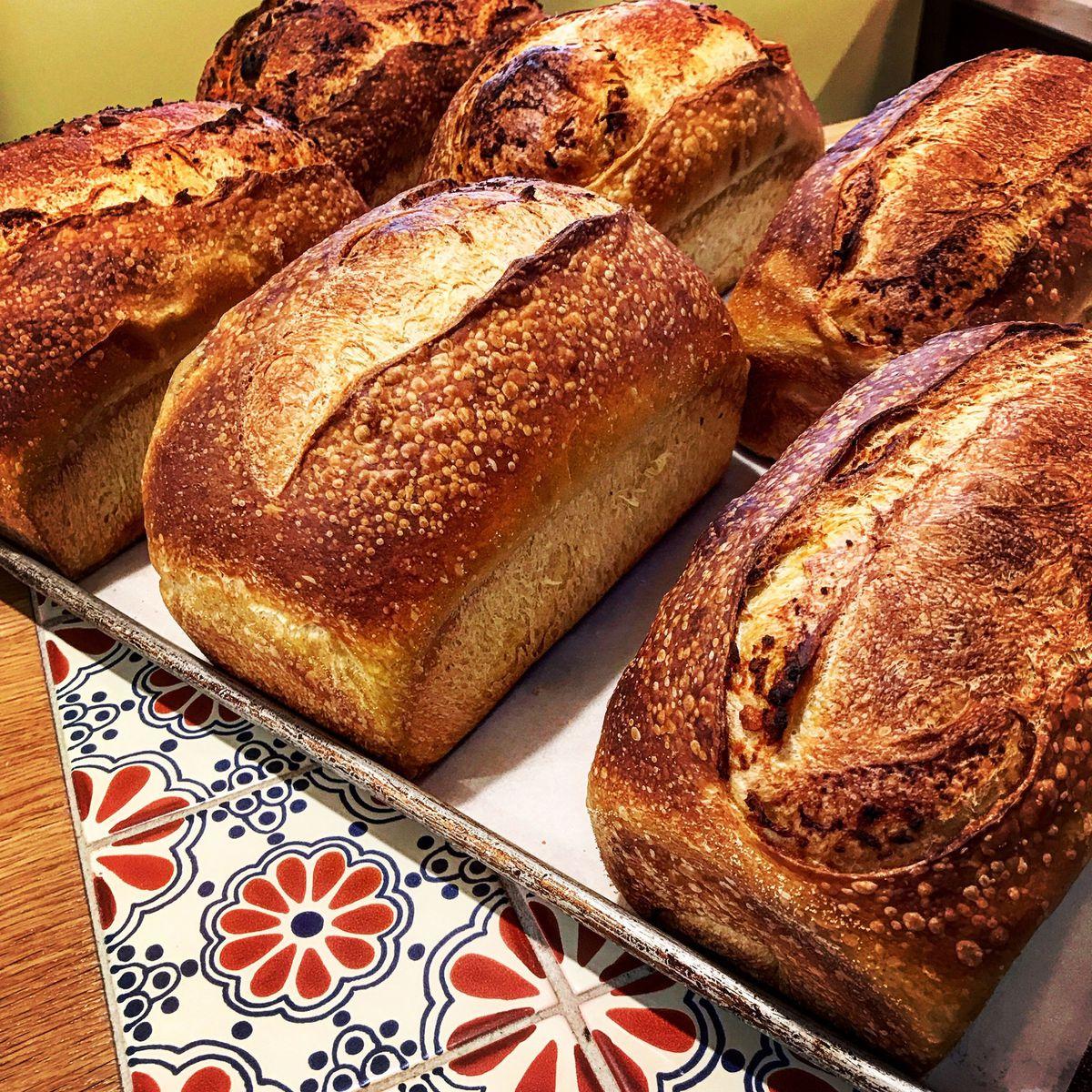 Six freshly baked sweet potato breads on a silver tray at La Calavera