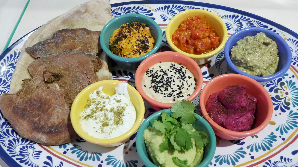 Seven small containers of bread dip in a rainbow of colors.