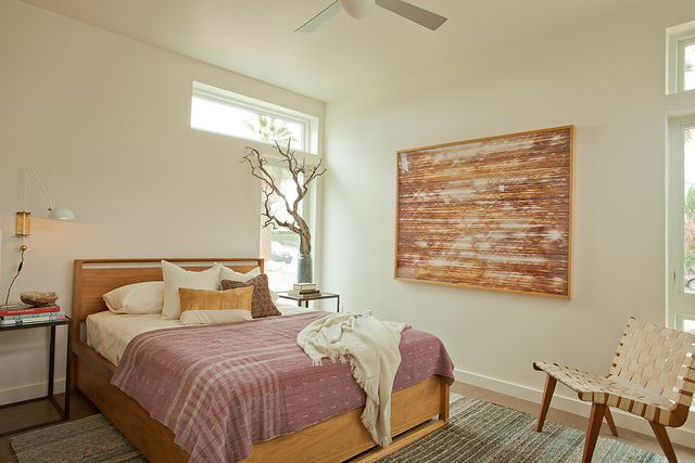 A bedroom with a bed that has a mauve patterned quilt and multiple pillows. There is a chair and two end tables. There is a large work of art hanging on one of the walls.