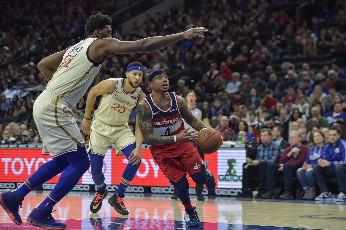 Washington Wizards guard Isaiah Thomas drives to the basket as Philadelphia 76ers center Joel Embiid defends during the first quarter of the game at the Wells Fargo Center.