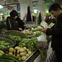 In this March 20, 2012 photo, a customer buys vegetable from a market in Shanghai, China. China's inflation edged up in March as the government shifted focus from containing politically dangerous price rises to stimulating its slowing economy. Consumer prices rose 3.6 percent over a year earlier, up from February's 3.2 percent, data showed Monday, April 9, 2012.