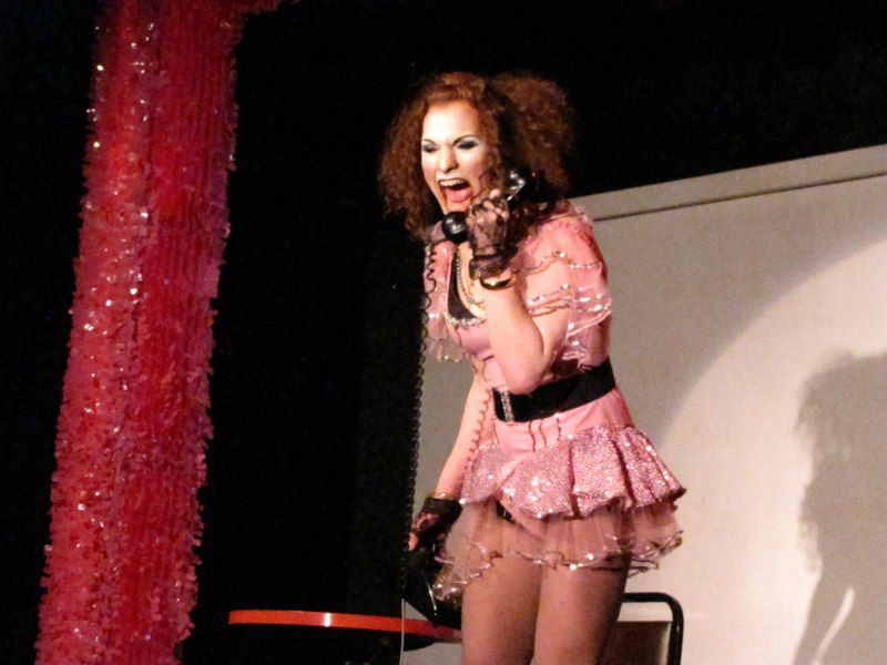 A person in a short pink dress and a crimped brown wig yells into the receiver of a rotary-dial telephone onstage.